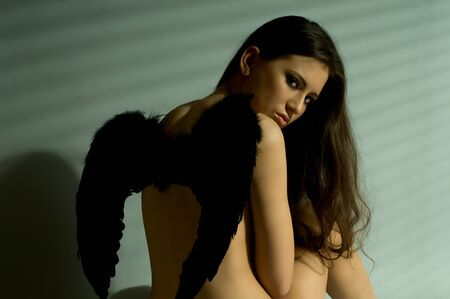 the very  pretty woman with black wings, light throug jalousie, hdark  long hair , sensual look... photo