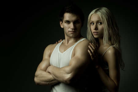 athletic type: muscular handsome sexy guy with pretty woman on dark background, look on camera Stock Photo