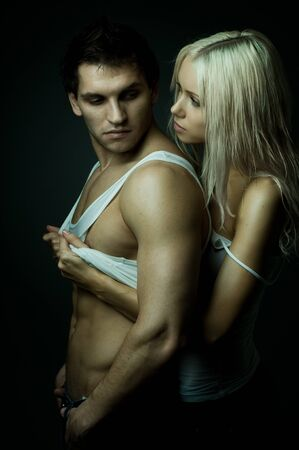 vehement: muscular handsome sexy guy with pretty woman, on dark background, glamour green light Stock Photo