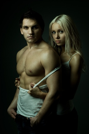 vehement: muscular handsome sexy guy with pretty woman, on dark background, glamour green light, look on camera
