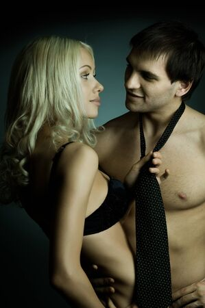 athletic type: muscular handsome sexy guy with pretty woman, on dark background, glamour  light
