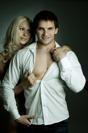 vehement: muscular handsome sexy guy with pretty woman, on dark background, glamour light, guy look on camera and smile Stock Photo