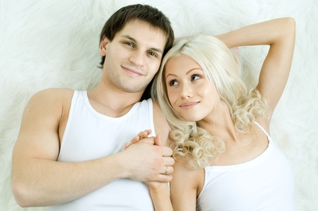 very happy  pretty couple, smile , look on camera and smile,  lie on white fur photo