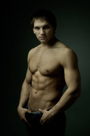 muscularity: the very muscular handsome sexy guy on dark background, strict