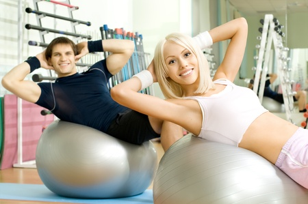 happy cutie athletic girl and guy,  execute exercise on muscles belly  on balls and smile, in  sport-hall photo