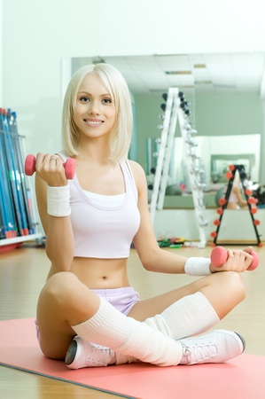 scrawny: happy cutie athletic girl ,  execute exercise  with dumbbells and smile, in  sport-hall