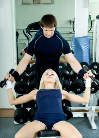 happy cutie athletic girl and guy,  exercise with dumbbells and smile, in  sport-hall Stock Photo - 9209027