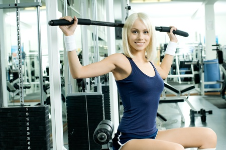 cutie: happy cutie athletic girl ,  execute exercise on sport-apparatus  and smile, in  sport-hall