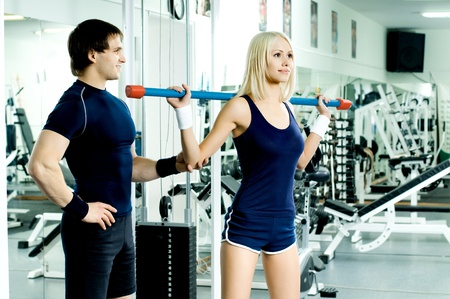 scrawny: guy instructor,  give instructions for cutie girl,  execute exercise and smile , in  sport-hall