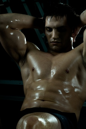 tough: very power athletic guy ,  execute exercise on muscles belly, in  sport-hall, beauty glamour light Stock Photo