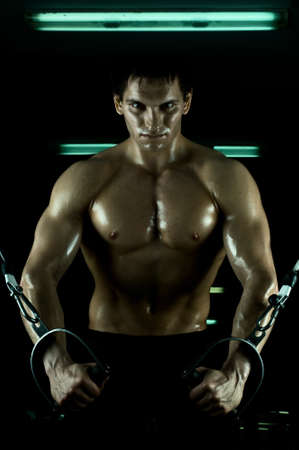 very power athletic guy ,  execute exercise on  on sport-apparatus, in  sport-hall, beauty glamour light photo