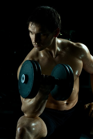 hardy: very power athletic guy ,  execute exercise with  dumbbells, in  sport-hall, beauty glamour light Stock Photo
