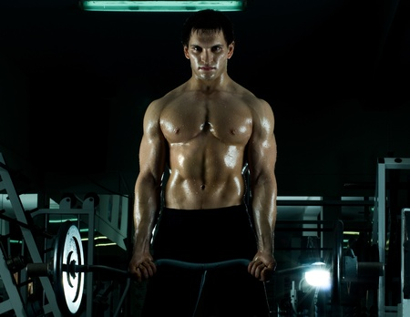 brawny: very power athletic guy ,  execute exercise with  weight, in  sport-hall, beauty glamour light