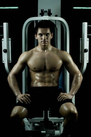 very power athletic guy ,  sit on  on sport-apparatus, in  sport-hall, beauty glamour light photo