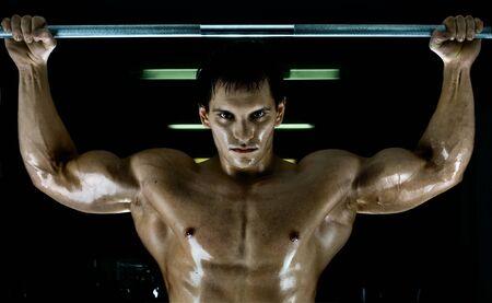 rekstok: zeer macht athletic guy, oefening aanscherping op horizontale balk, in sport-hall, glamour licht uitvoeren, stare kijk op camera Stockfoto