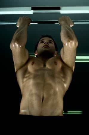 rekstok: zeer krachtige atletische man, uit te voeren uit te oefenen vast op horizontale balk, in de sport-hal, glamour licht