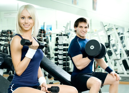 svelte: happy cutie athletic girl and guy,  exercise with dumbbells and smile, in  sport-hall