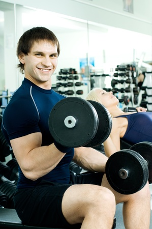cutie: happy cutie athletic guy,  exercise with dumbbells, in  sport-hall, look on camera and smile