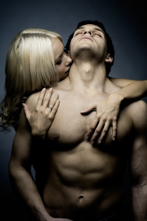 vampira sexy: muscular tipo sexy guapo con una mujer bonita, sobre fondo oscuro, luz de glamour Foto de archivo