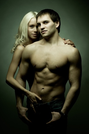 svelte: muscular handsome sexy guy with pretty woman on dark background, look on camera, glamour green light