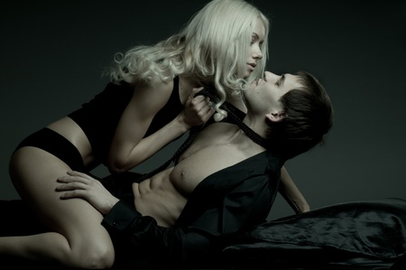 passionate embrace: muscular handsome sexy guy with pretty woman, on dark background, glamour  light