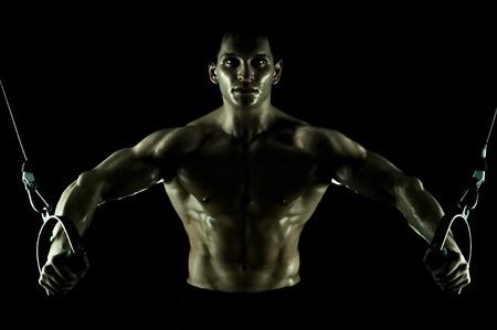 sportsman: muy potencia atl�tica chico, ejecutar el ejercicio en el deporte-aparato, en el deporte-hall, sobre fondo negro, aislado