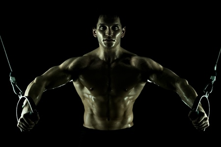 sportsman: very power athletic guy ,  execute exercise on  on sport-apparatus, in  sport-hall, on black background, isolated