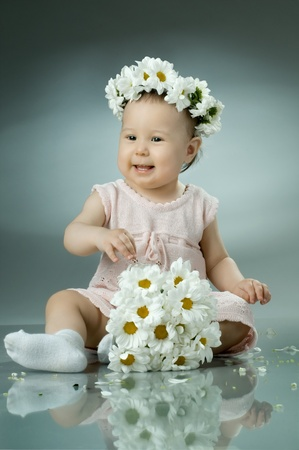 beautiful  little kid with  bouquet and diadem of flowers , sit and  smile  photo