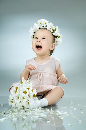 beautiful  little kid with  bouquet and diadem of flowers , sit and  smile Stock Photo - 10084550