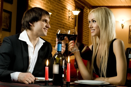 date: romantic evening date in hotel room, or supper in restaurant, happy couple with wine glass