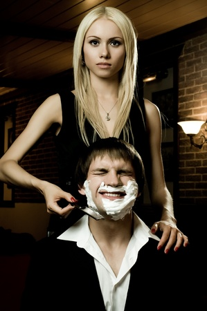 imperturbable: beautiful youth woman  with blindfold,  get shave guy  hazardous razor Stock Photo