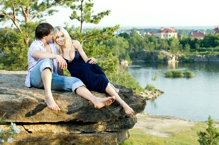 courting: romantic  date on nature, happy couple sit aloft on rock  with beautiful view