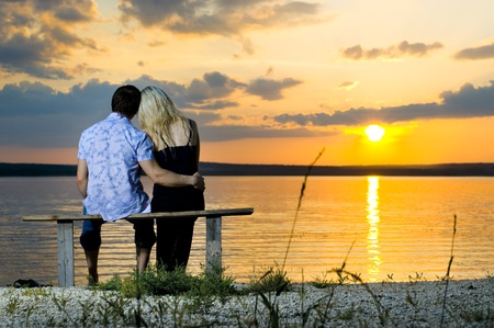 courting: romantic evening date on nature, couple on beautiful sunset on  lake