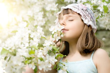 The beautiful little girl, with bush blossoming apple-tree, smell flowers, opposite sun light