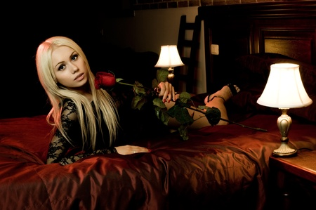 impassioned: the beautiful  young woman lie on  bed with rose, in hotel room
