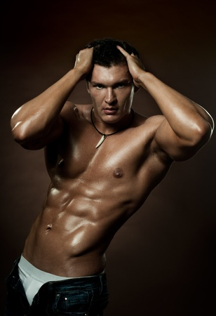 the very muscular handsome sexy guy on dark  brown background, strict Stock Photo - 11219953