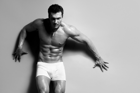 man underwear: the very muscular handsome sexy guy on   grey background, strict