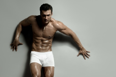 the very muscular handsome sexy guy on   grey background, strict photo