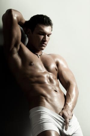 bloke: il bel ragazzo molto muscoloso sexy su sfondo grigio, stretto Archivio Fotografico