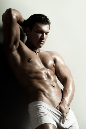 manly: the very muscular handsome sexy guy on   grey background, strict