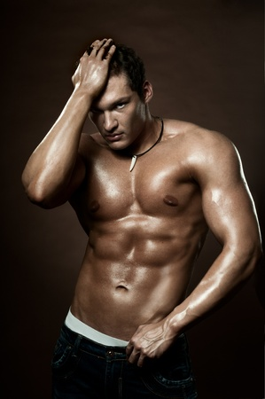 manly: the very muscular handsome sexy guy on dark  brown background, strict