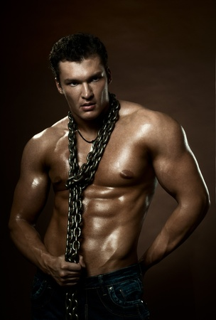 neckcloth: the very muscular handsome sexy guy on dark  brown background, with neckcloth of  chain on neck Stock Photo