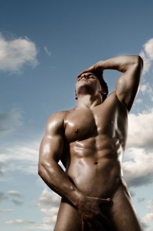 nude outdoors: the very muscular handsome sexy guy on dark background, posture Stock Photo