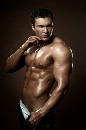athletic type: the very muscular handsome sexy guy on dark  brown background, strict