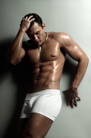 jungen unterwäsche: die sehr muskulös schön sexy Kerl auf grauem Hintergrund, strikte