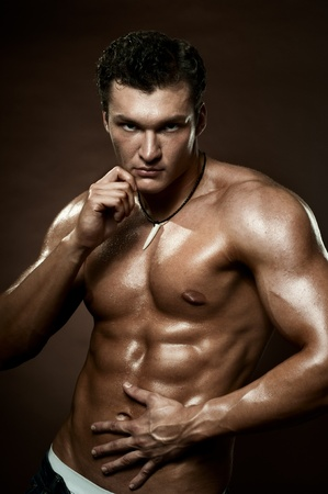 manly man: the very muscular handsome sexy guy on dark  brown background, strict