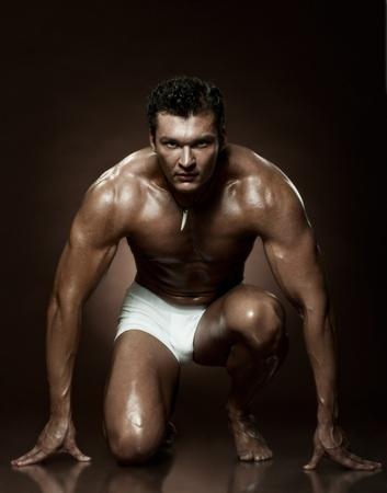 hombre flaco: la muy musculoso chico guapo sexy en fondo oscuro marr�n, estricta Foto de archivo
