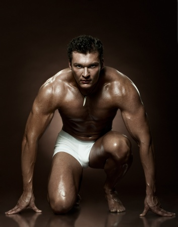 young man portrait: the very muscular handsome sexy guy on dark  brown background, strict
