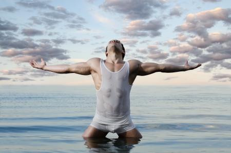 il bel ragazzo muscoloso, sexy sul cielo e lo sfondo del mare