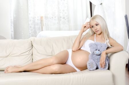 pregnant underwear: young pregnant woman lie  on white sofa in light  home room Stock Photo